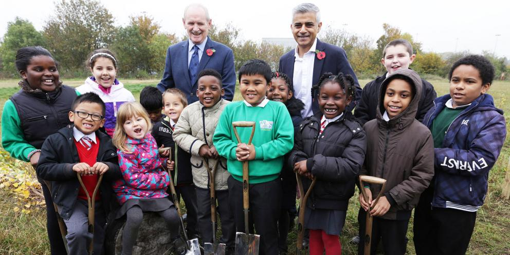 Sadiq with children planting a tree