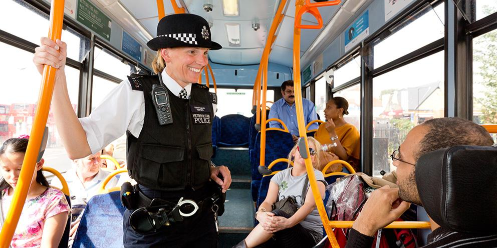 Police officer speaks with member of the public on a bus