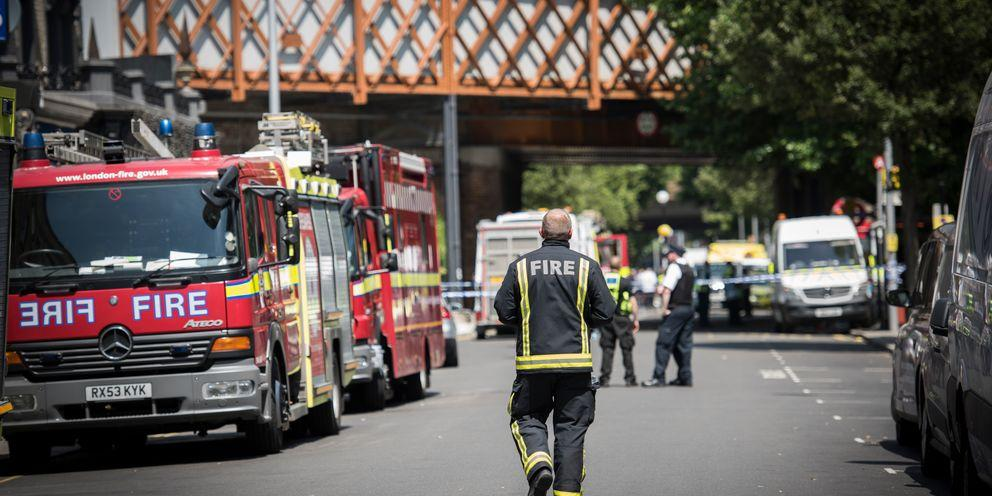 Fire trucks and firefighter outside of Grenfell Tower