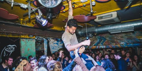 Man crowd surfing in small London club