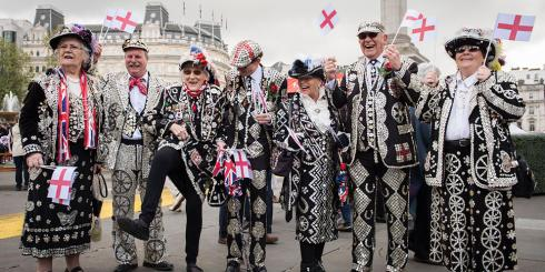Pearly kings and queens waving flags at the Feast of St.George