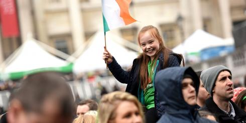 Girl holding the Irish flag on St Patrick's Day in Trafalgar Square