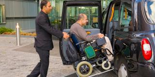 Porter pushing guest in wheelchair into accessible taxi
