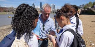 School children study stones from the banks of the Thames