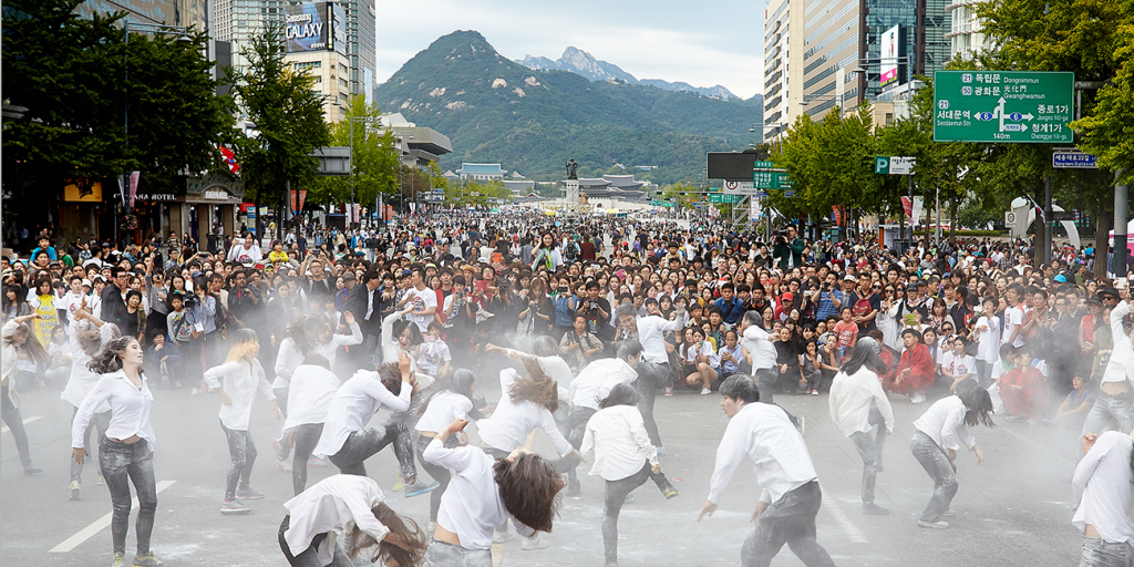 Dancers performing on a road in front of a crowd