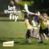 Brownies running with model airplane with caption 'let them fly'