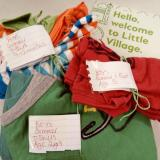 Image of clothes folded with size and gender labels and Welcome to Little Village leaflet.
